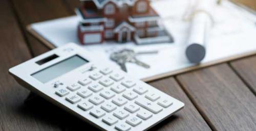 calculatrice devant un modele de maison de villa